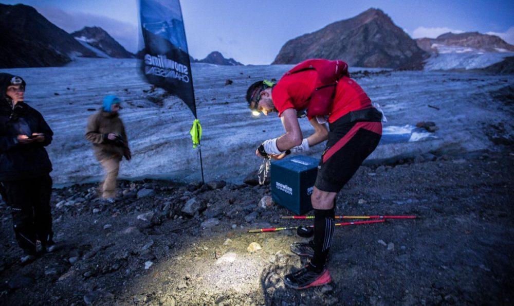 Martin Schedler (Team Salomon Deutschland) zieht vor der Gletscherquerung die Grödel über.