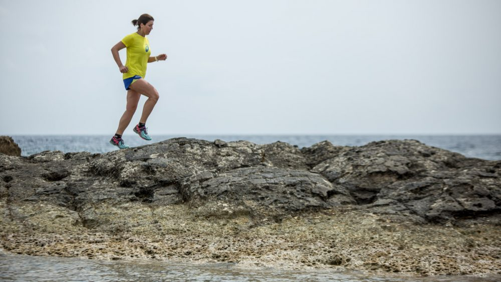 Nicole balanciert auf nassem Fels im Meer