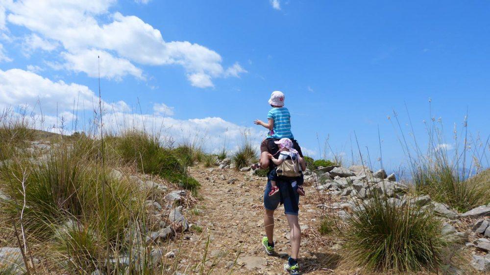 Gregor mit seinen Töchtern auf dem Rücken unterwegs zum Gipfel